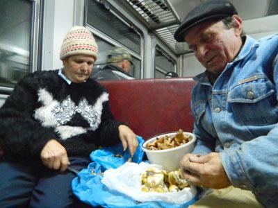 Анатолий Балакин и Любовь Гарнага чистят собранные грибы в электричке по пути в Ясиноватую.